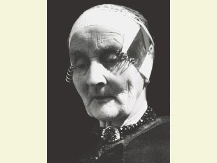 Vrouw uit Oldebroek in rouwdracht. Zij draagt een zwartbonte tipmuts en een zilveren slot met zg. 'gitten'. Dit type slot wordt ook wel .zeven-steentjesslot. genoemd; een steen in het midden en zes er omheen  Foto: Jac. Gazenbeek (klik om te vergroten)