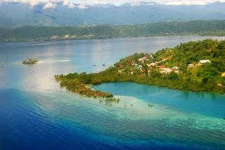 Manokwari. De verkleuring in het water is een enorm koraalrif