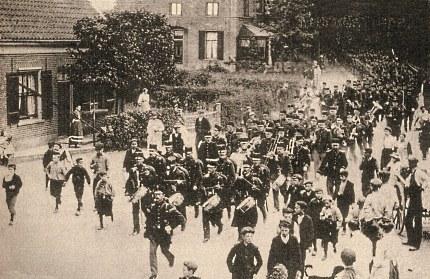 Intocht van de twee bataljons 11 RI met voorop het regimentsmuziekkorps op de Arnhemseweg / hoek Grotestraat in Ede. De dorpsjeugd, veelal op klompen, loopt mee met de soldaten (Foto: Gemeentearchief Ede) klik om te vergroten