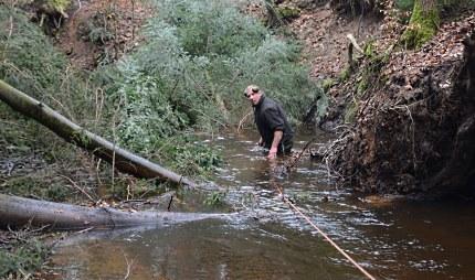 Douwe, de aangever, staat tot aan zijn middel in het water.