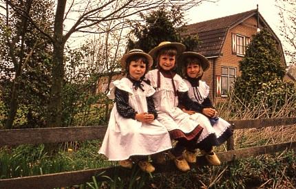 Drie kleine kleuters op een hek
