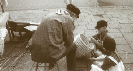 Tijdens de Oud Lunterse Dag van 1999 worden Rien en Eva van Dijk ingewijd in het moeilijke werk van korven vlechten door de voorzitter de heer De Koning