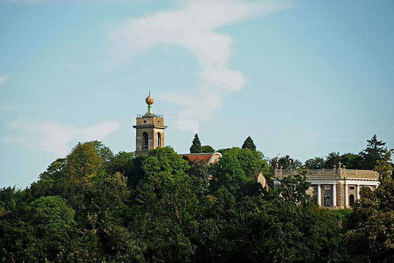 De oude St.Lawrence Church met goudkleurige bol is op grote afstand in de omgeving zichtbaar. Het familie Dashwood mausoleum is net -rechts- zichtbaar.