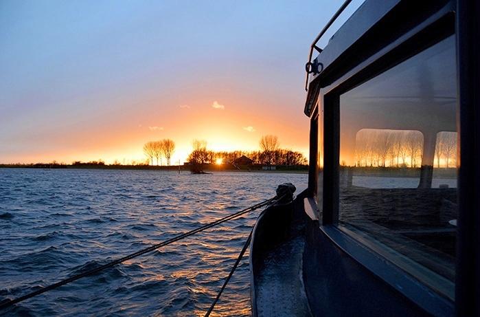 De ondergaande zon zet het schip in een schitterend licht - Foto: ©Louis Fraanje