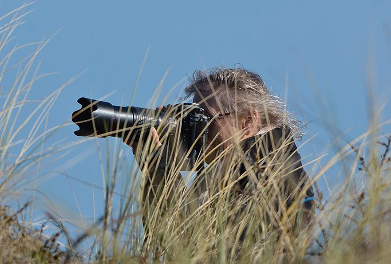 Boven op het duin zit Fransien met de camera in de aanslag - Foto: ©Louis Fraanje