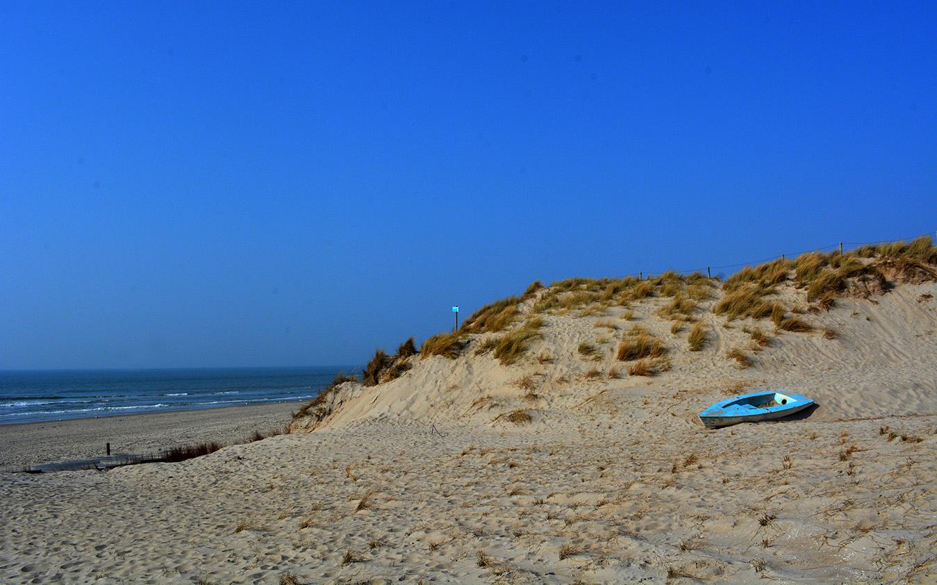 De zee is zichtbaar en onderaan het duin ligt een bootje – Foto: ©Louis Fraanje