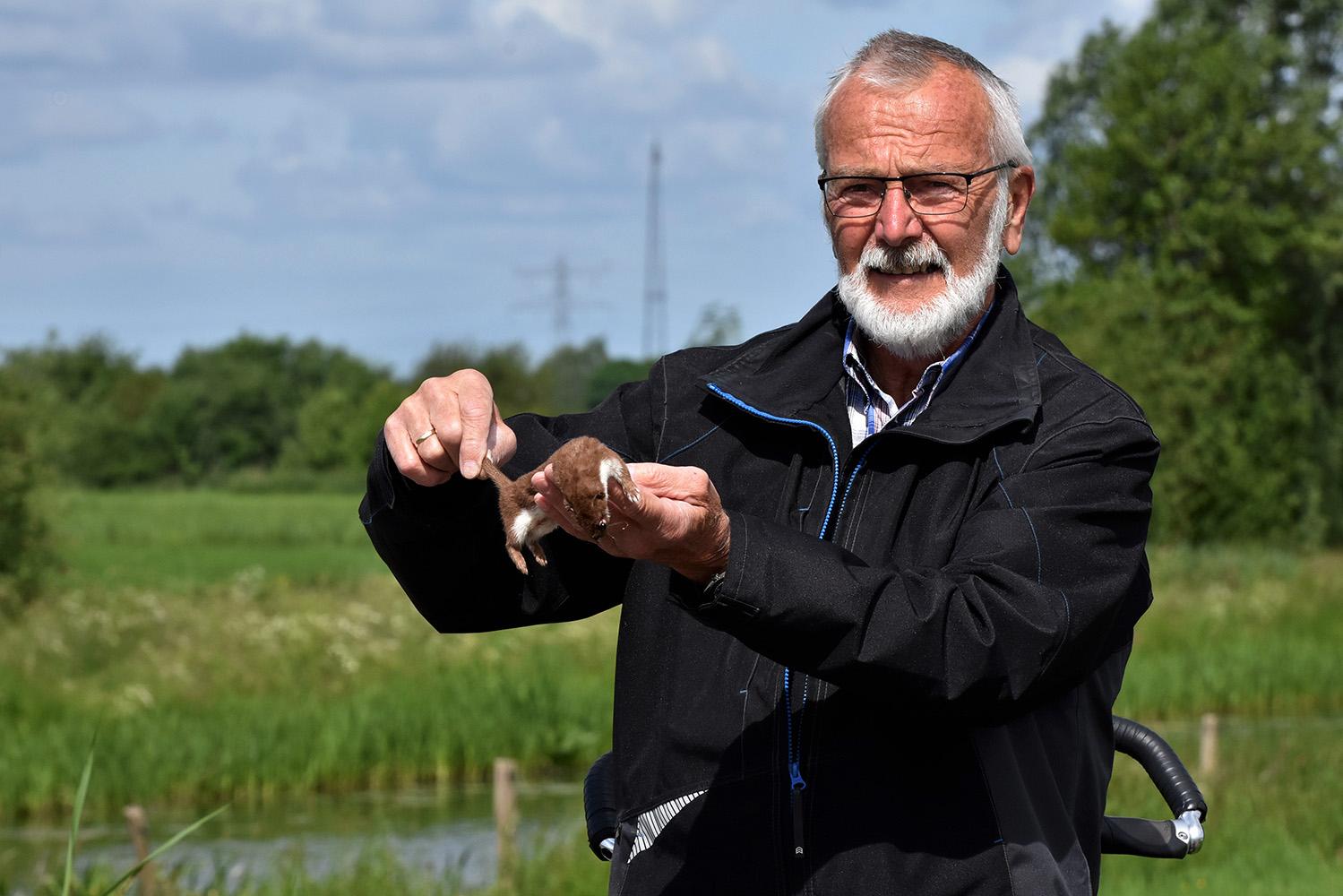 Natuurliefhebber Dick Teunissen met het doodgereden wezeltje - Foto: ©Louis Fraanje