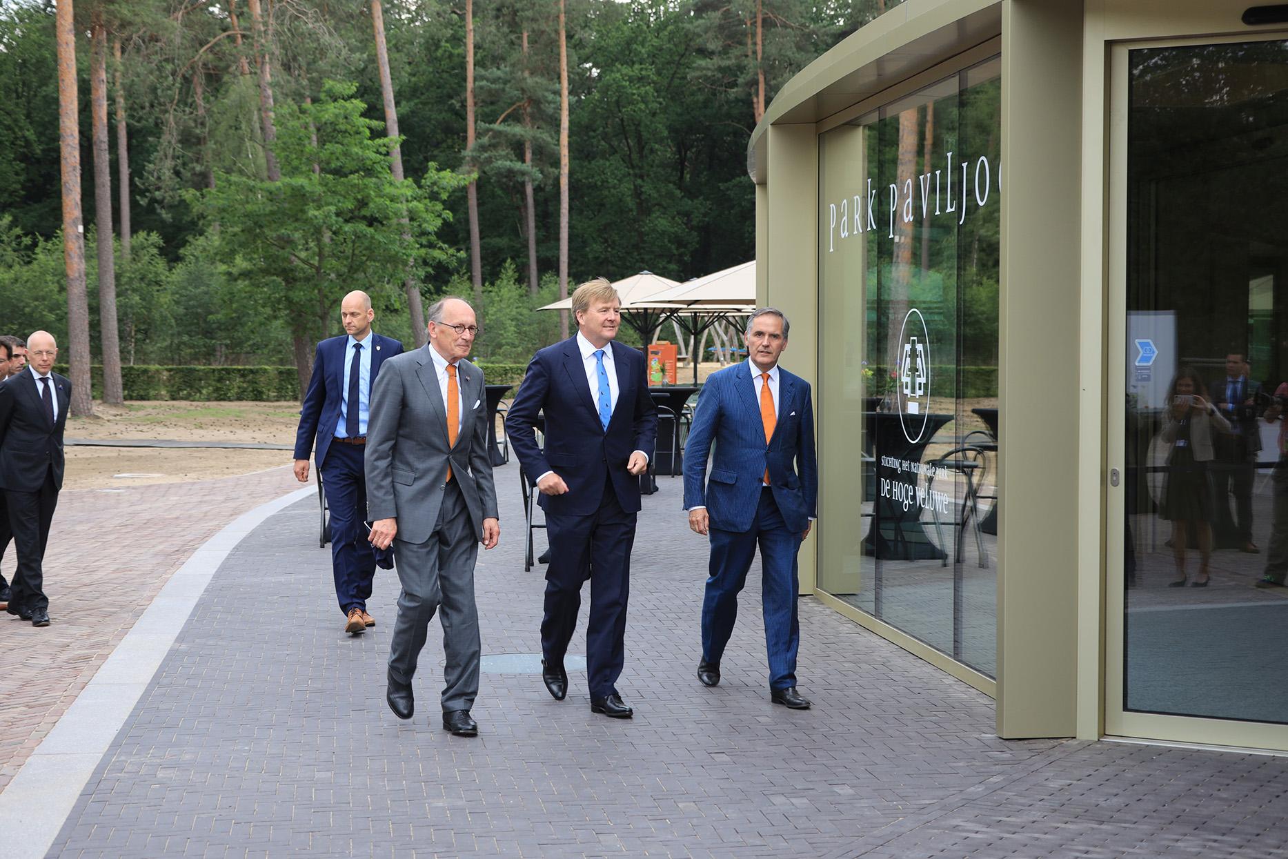 De Koning, geflankeerd door onder meer gastheer Seger van Voorst tot Voorst, directeur/bestuurder van Het Nationale Park De Hoge Veluwe, als eerste het nieuwe publieksgebouw binnen - Foto: ©NP De Hoge Veluwe