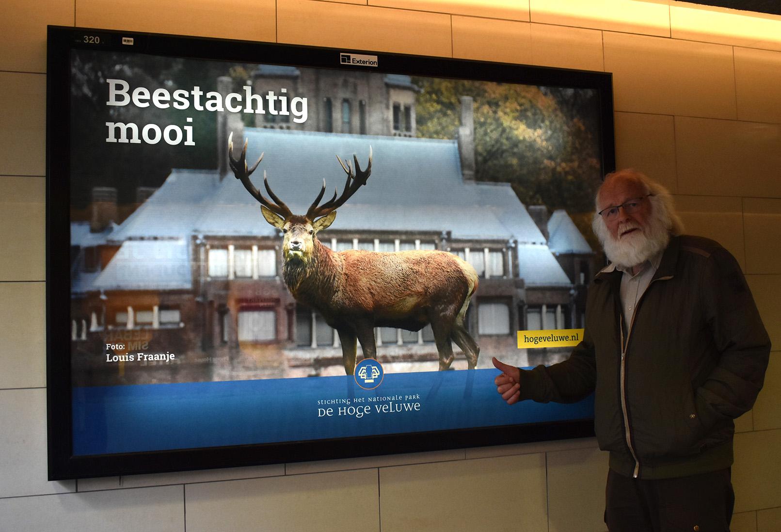 Een trotse fotograaf bij zijn winnende foto als 'spread' op het station – Foto: ©Fransien Fraanje