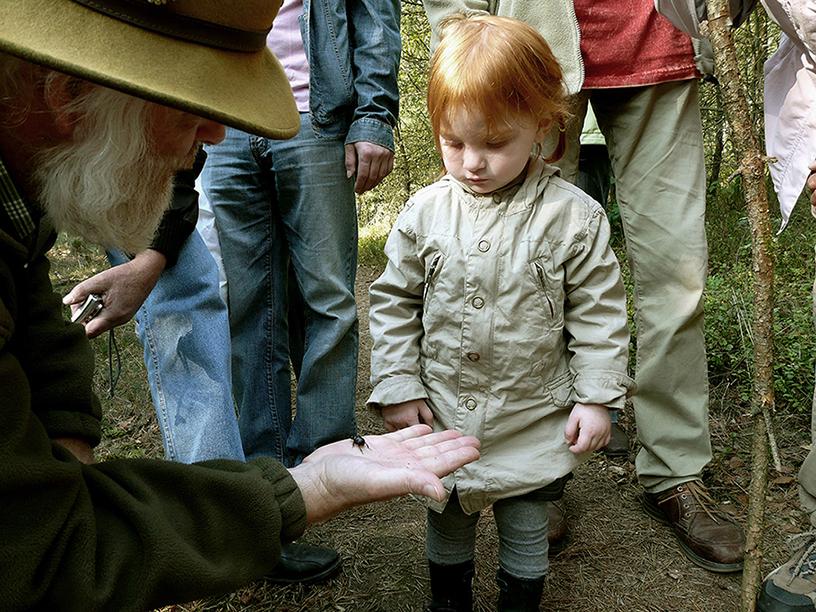 Louis tijdens een natuurwandeling laat dit kleine meisje een mestkever op zijn hand - Foto: ©Fransien Fraanje