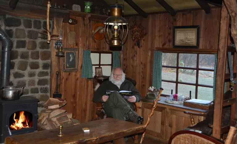 Louis lezend in het fotoboek bij de warme kachel in de jachthut – Foto: ©Fransien Fraanje