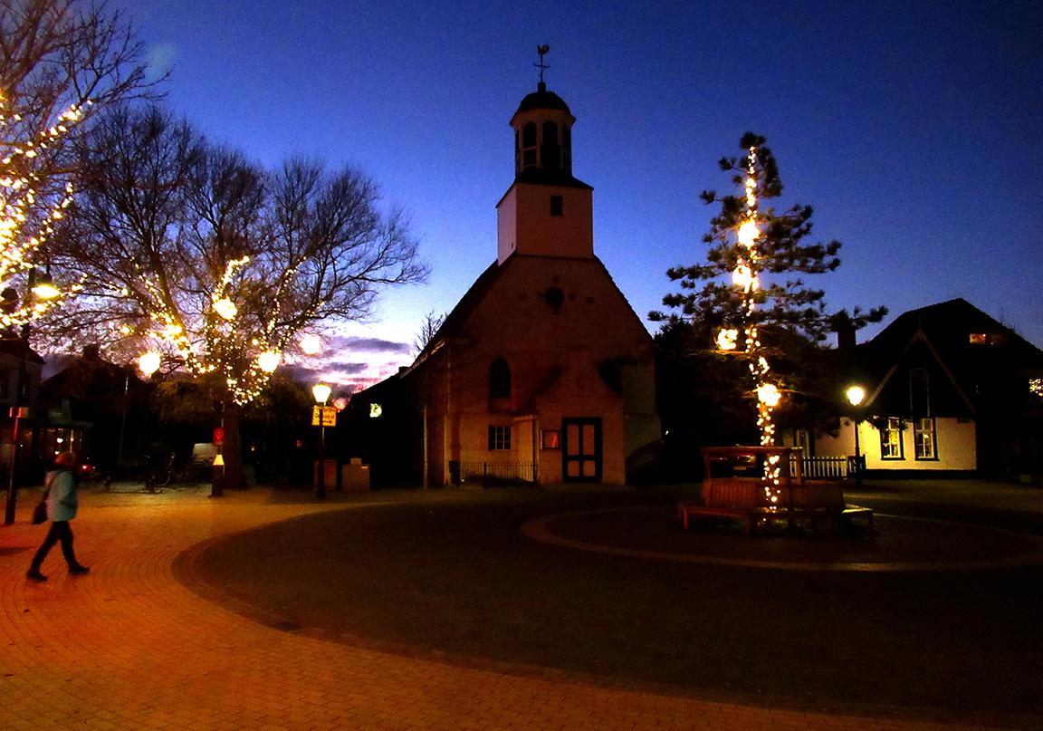 Op het plein bij de kerk zijn de bomen voorzien van Kerstverlichting – Foto: ©Louis Fraanje