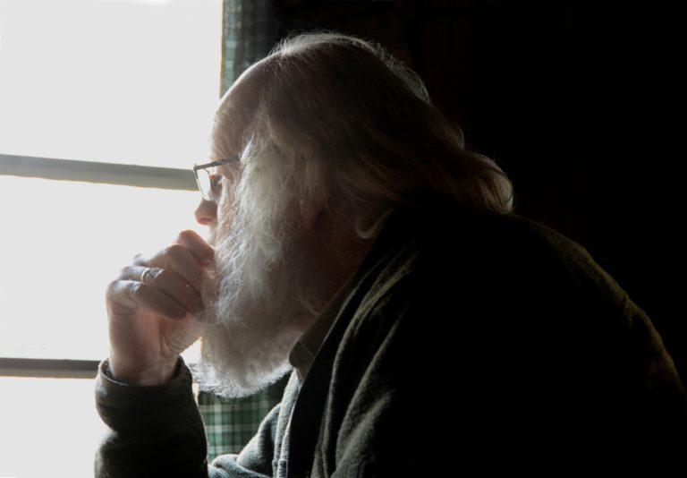 Veluwenaar Louis zit in gedachten voor het raam van de jachthut – Foto: ©Fransien Fraanje
