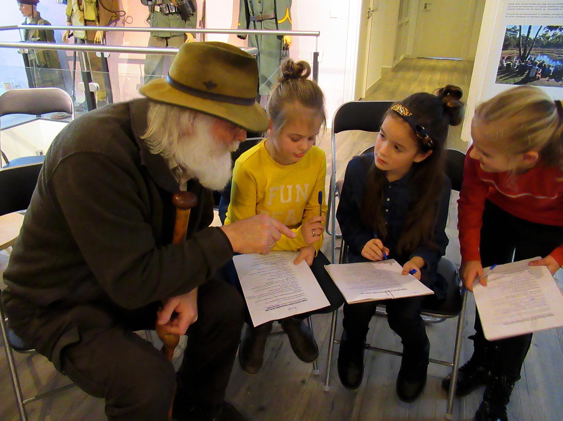 Tijdens het beantwoorden van de vragenlijst legt Louis nog het e.e.a. uit aan de kinderen - Foto: ©Jac. Gazenbeekstichting