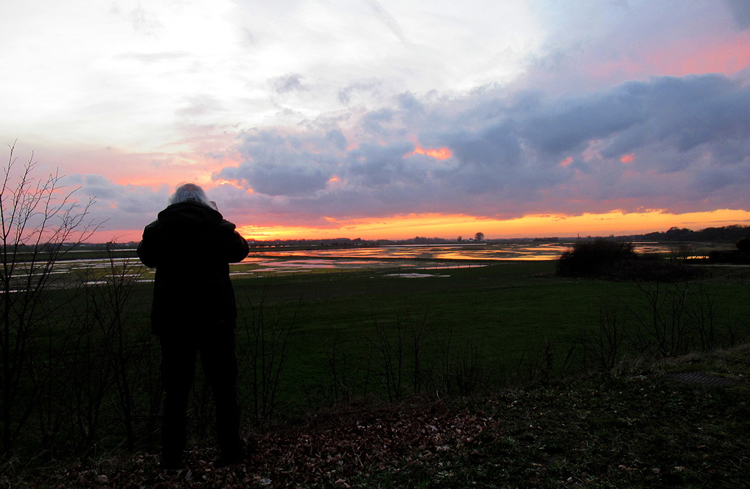 Louis staat te fotograferen bij de Rijn in een kleurrijke omgeving - Foto: ©Fransien Fraanje