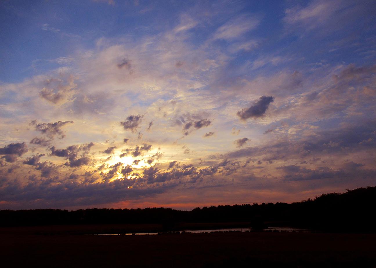 Als de zon door het wolkendek probeert heen te komen is dat telkens weer een kleurrijk schouwspel – Foto: ©Louis Fraanje