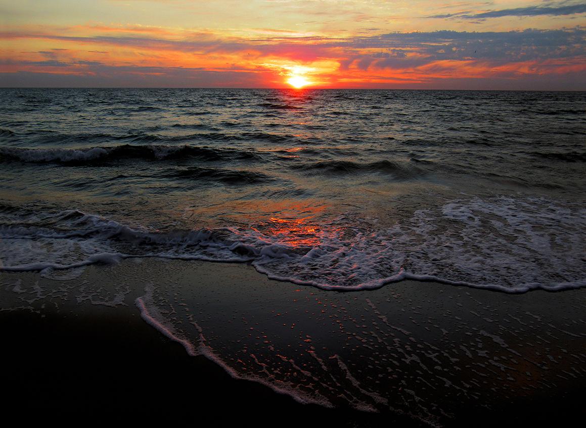 Mooi avondrood boven de horizon, met weerspiegeling in de branding - Foto: © Louis Fraanje