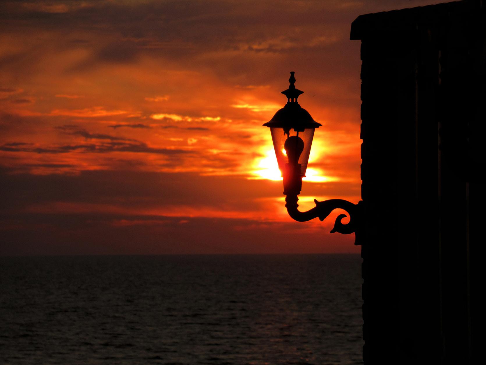 Avondstemming met het laatste zonlicht door de lantaarn (zonne-energie) van het restaurant aan zee - Foto: © Louis Fraanje