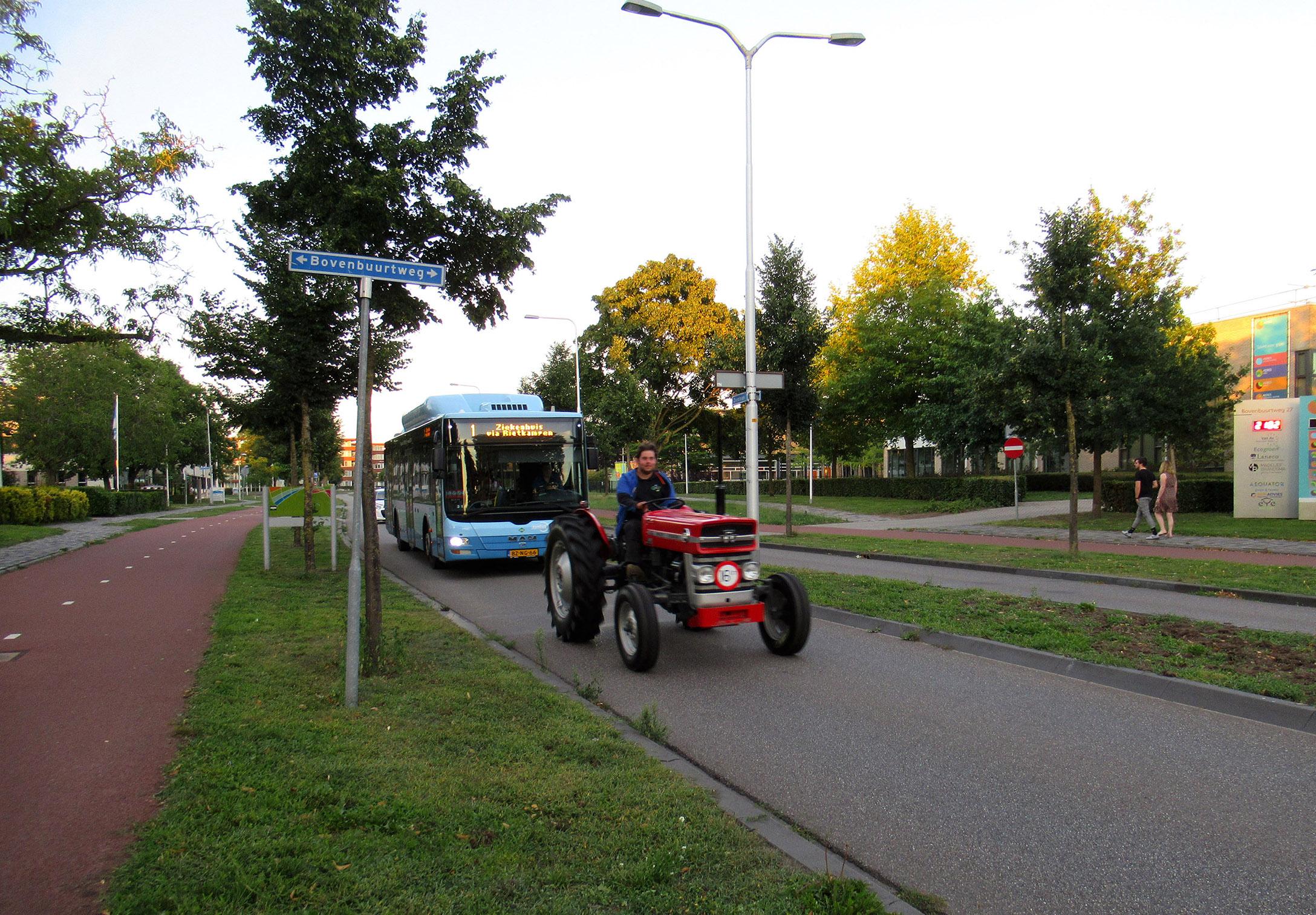 Als we de Zandlaan oversteken komt er net een trekker voorbij met de lijnbus en een aantal auto's in zijn kielzog. En een breed lachende bestuurder... van de trekker bedoel ik dan! - Foto: ©Louis Fraanje