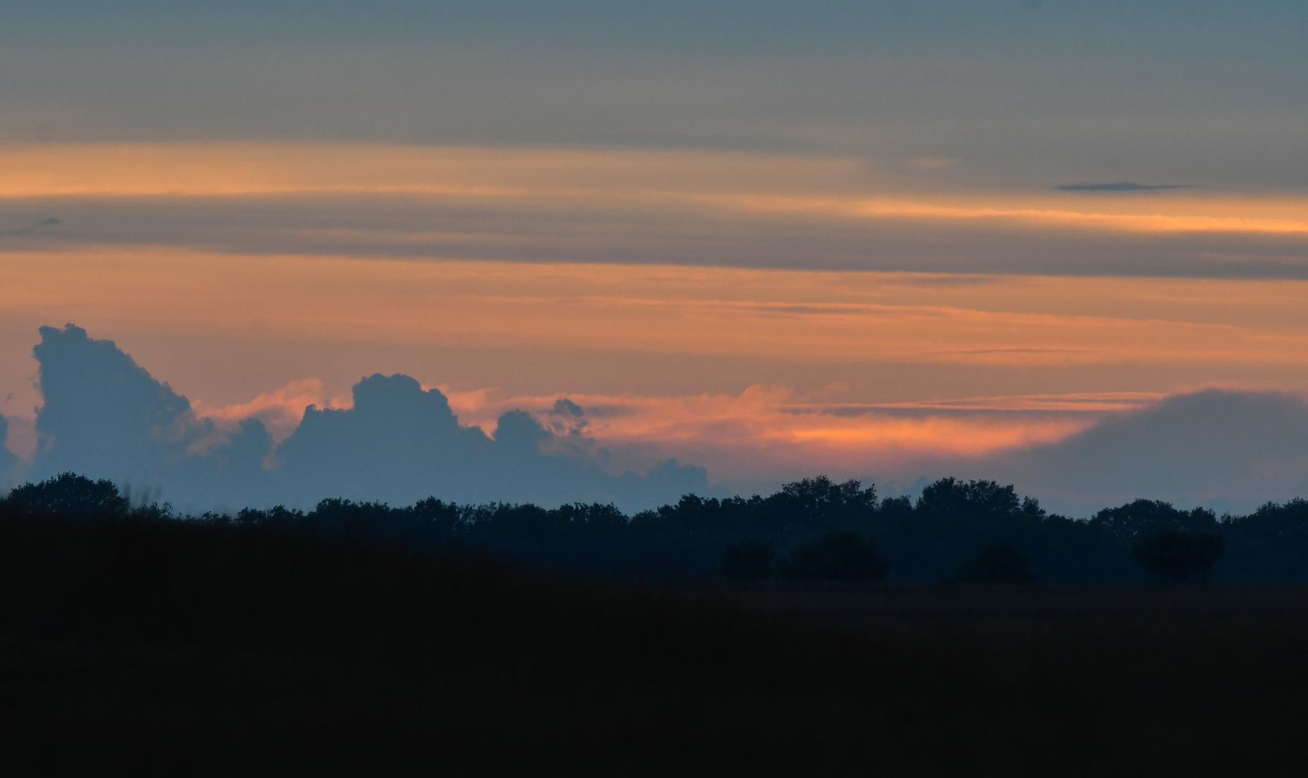 Boven Oud Reemst kleurt de avondhemel rood tussen de donkere wolken door – Foto: ©Louis Fraanje