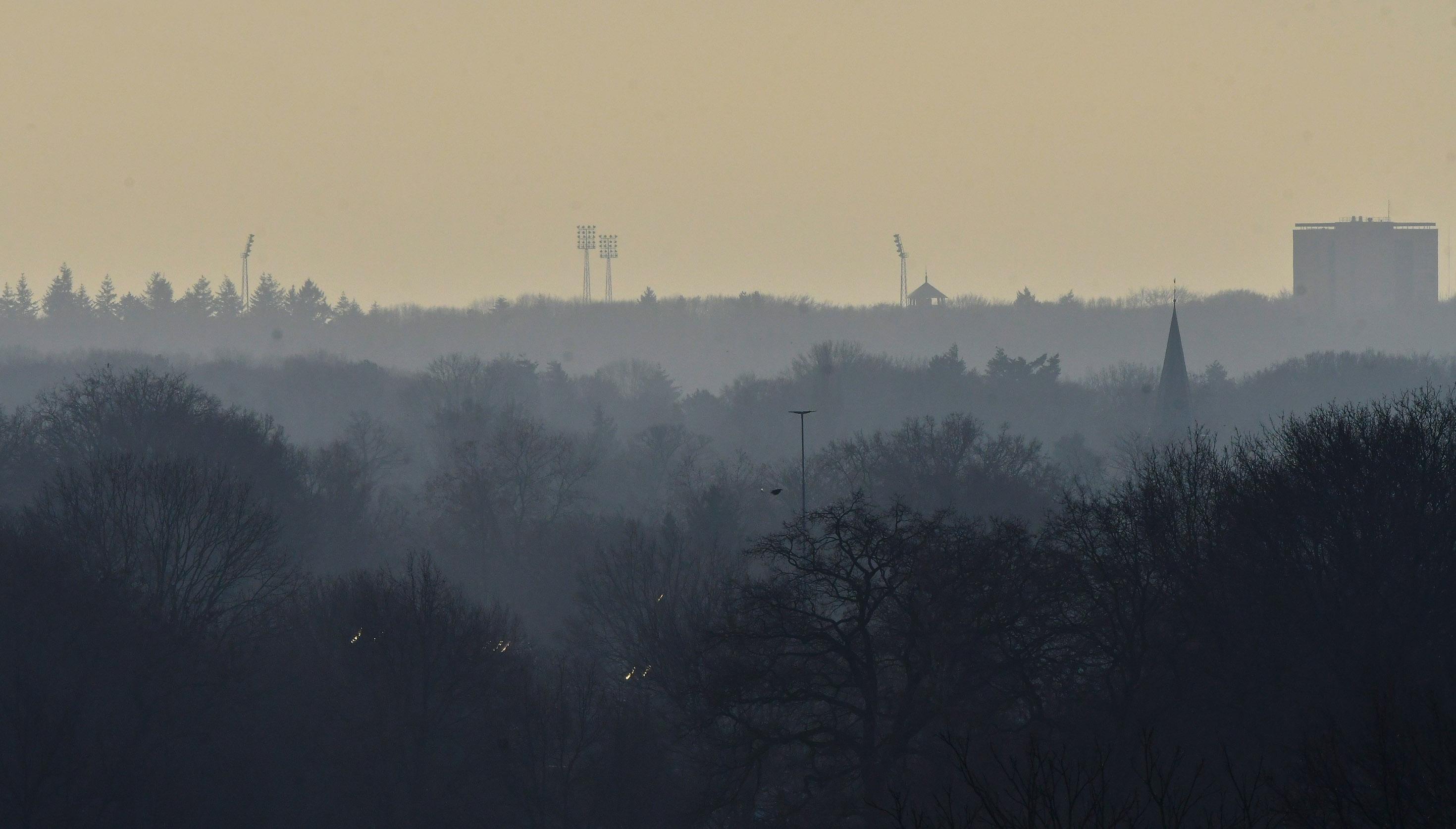 Aan de horizon de hoge masten met lampen van het oude voetbalstadion De Wageningse Berg - Foto: ©Louis Fraanje
