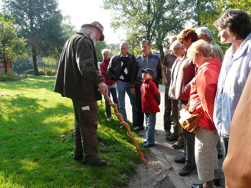 Natuurgids en verhalenverteller Louis Fraanje met een groep wandelaars op Landal GreenParks De Miggelenberg. Terwijl Louis uitleg geeft, kijkt en luistert de jongen met veel interesse naar hem - Foto: ©Fransien Fraanje