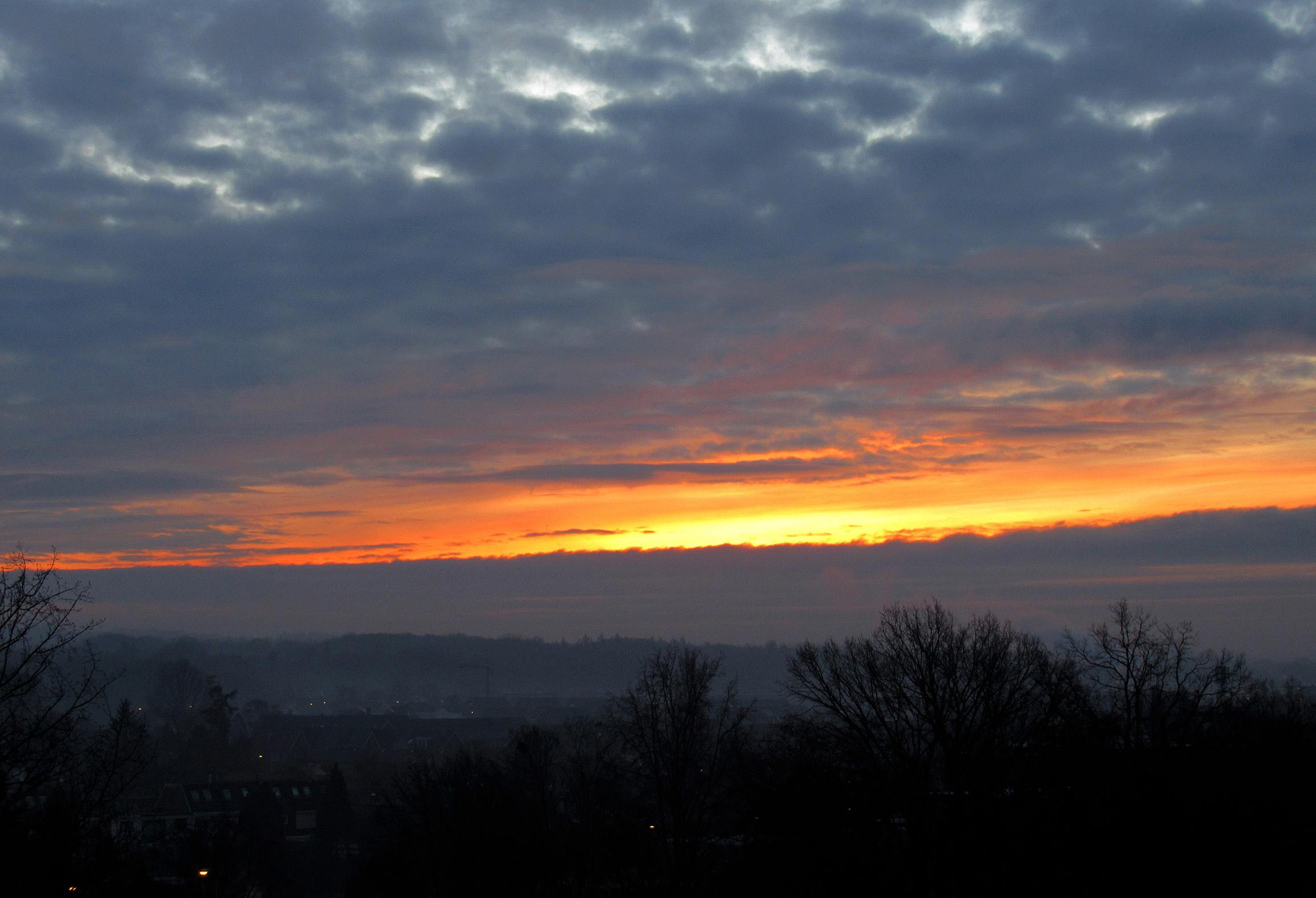 Tussen de grijze wolken door, gloorde een prachtig en kleurrijk begin van deze Nieuwjaarsdag - Foto: ©Louis Fraanje