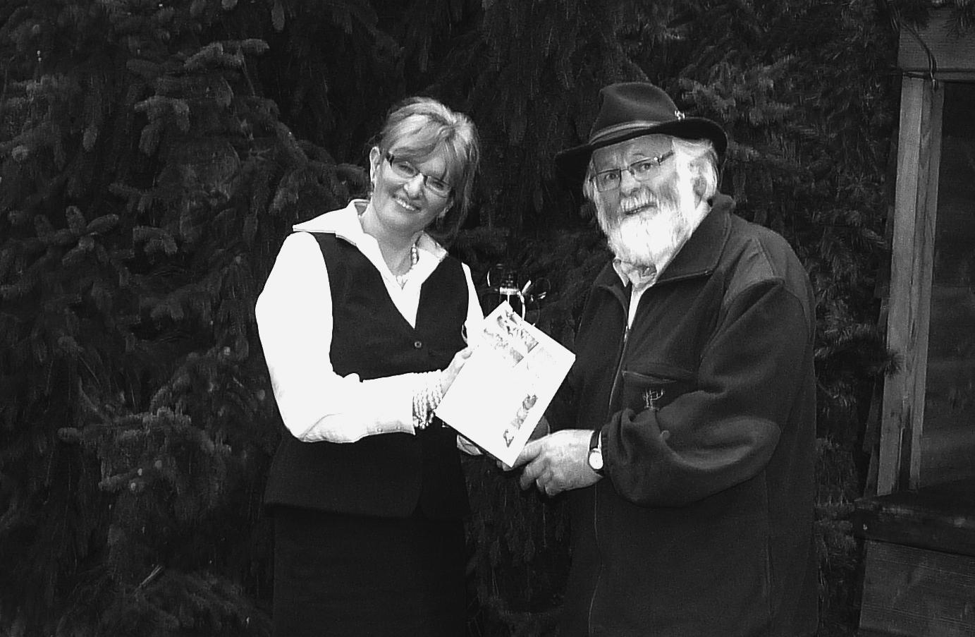Yvonne Borneman van LandalGreen Park De Miggelenberg overhandigd Louis Fraanje, zichtbaar onder de indruk, de envelop, met daarin de coupon voor het gratis weekend op Landal Miggelenberg, en de bijbehorende fles wijn - Foto: Judith Kok