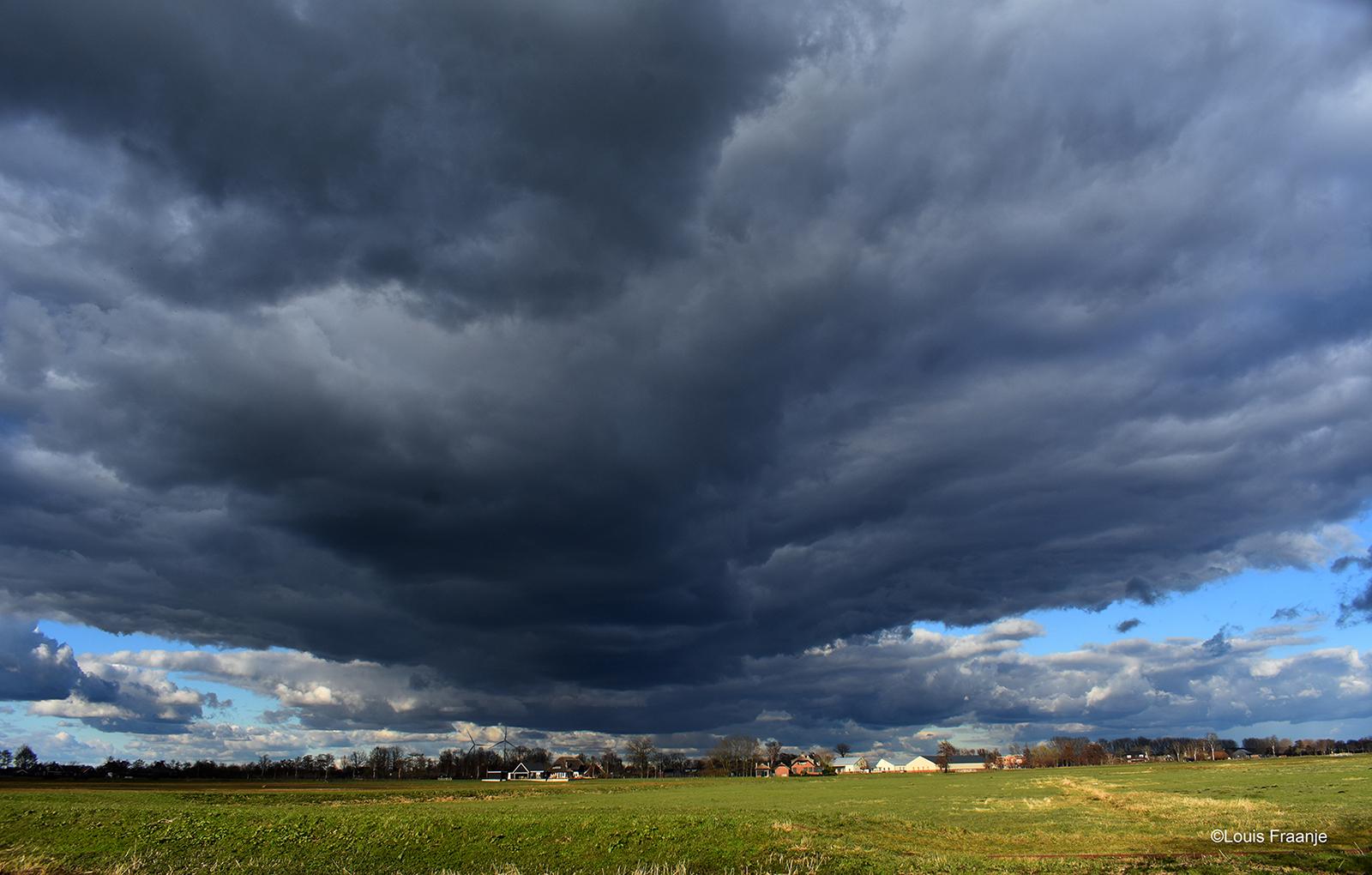 Een dreigende wolkenlucht boven de Meentweg in het Binnenveld - Foto: ©Louis Fraanje