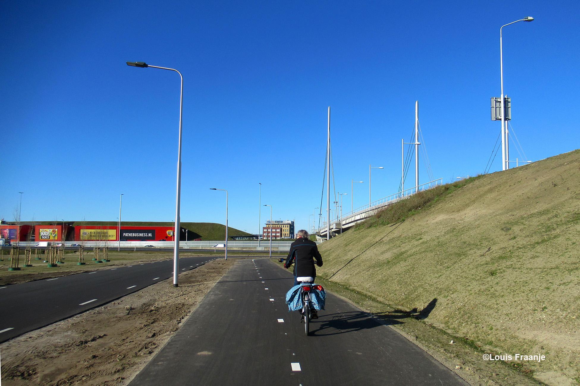 En dan komen we vanuit De Kraats over de Maanderdijk fietsen en zijn we alweer bijna thuis in Ede, links aan de overkant van de snelweg zien we de Cinemec-Pathé en rechts De Poortwachter. Het moet allemaal nog een beetje begroeid raken, maar het is mooi aangelegd! Pluim voor Ede! - Foto: ©Louis Fraanje