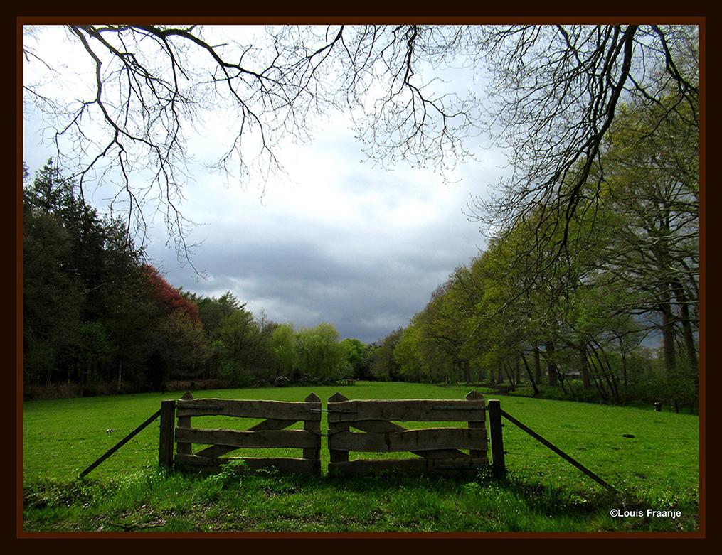 Het mooie houten hek, en daarachter een decor met prachtige tinten groen- Foto: ©Louis Fraanje
