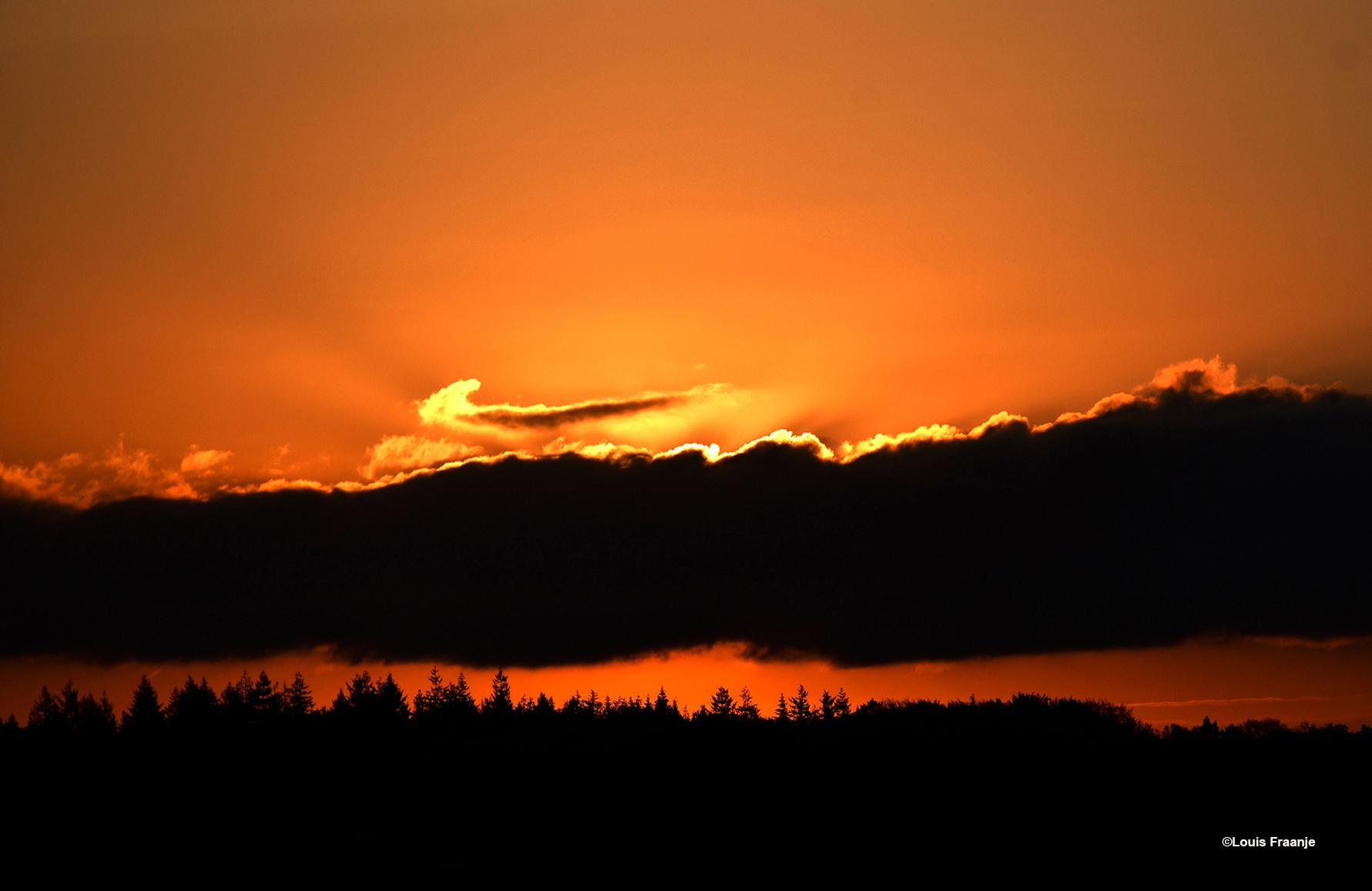 Een donkere wolkenbank boven de horizon, waarachter de opkomende zon heel even verdween- Foto: ©Louis Fraanje
