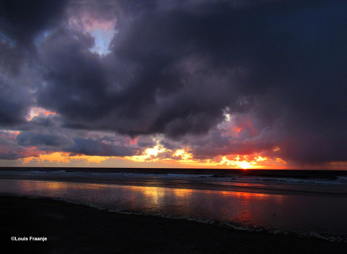 Een dreigende en tegelijkertijd schitterende avondlucht weerspiegeld in de vloedlijn – Foto: ©Louis Fraanje