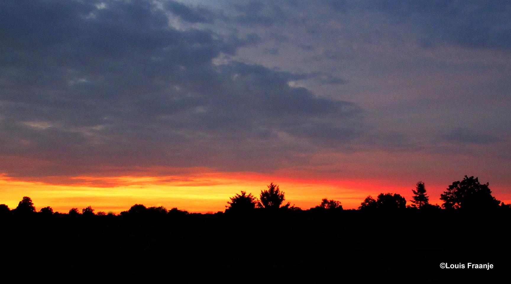 Onderaan de donkere avondlucht, kleurde vanavond de hemel vlammend rood - Foto: ©Louis Fraanje