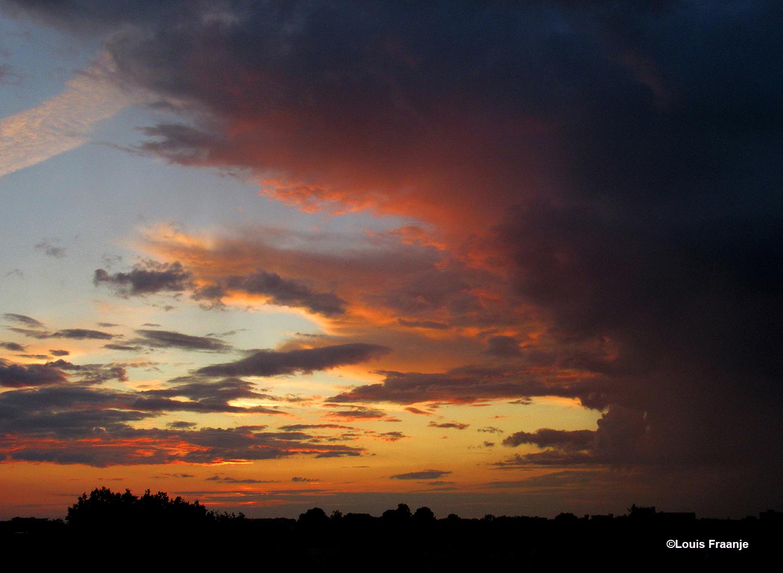 Een deel van de donkere wolkenlucht trok open en vormde zich een vlammend avondrood - Foto: ©Louis Fraanje