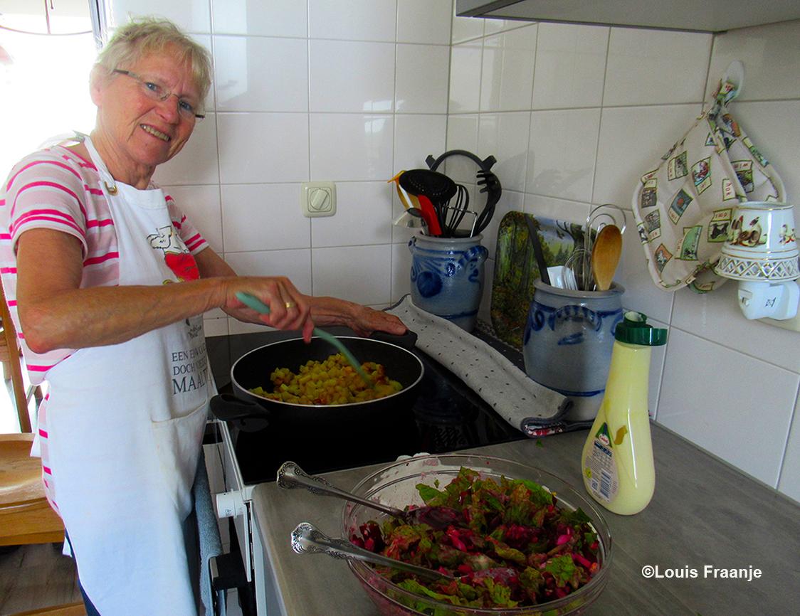 Een lachende kokkin is bezig met het eten - Foto: ©Louis Fraanje