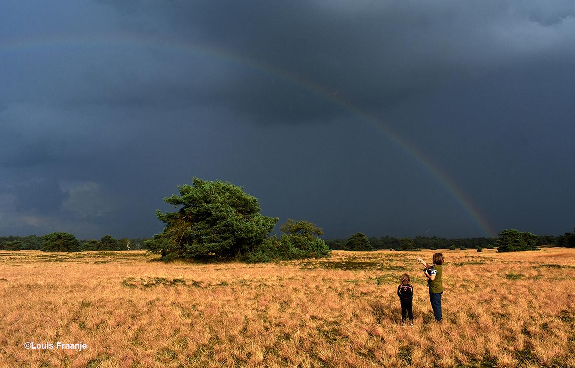 Twee kinderen daar midden in de natuur 'oog in oog' met de regenboog - Foto: ©Louis Fraanje