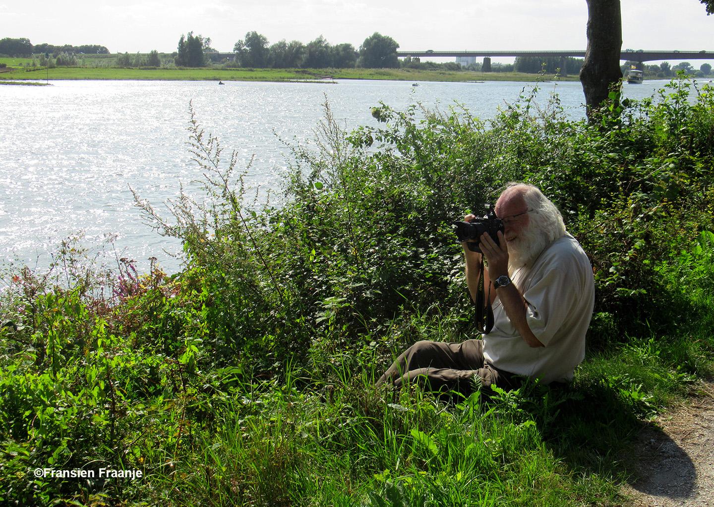 Louis zit heerlijk in de berm tussen het fietspad en de rivier, met op de achtergrond de brug over de Nederrijn bij Rhenen - Foto: ©Fransien Fraanje