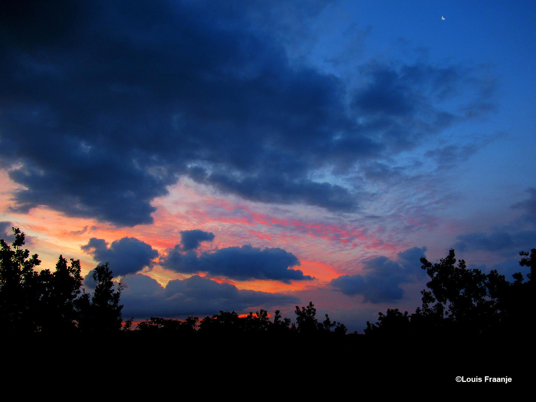 Een prachtig schouwspel, waarbij helemaal rechtsboven het maantje nog net zichtbaar is - Foto: ©Louis Fraanje
