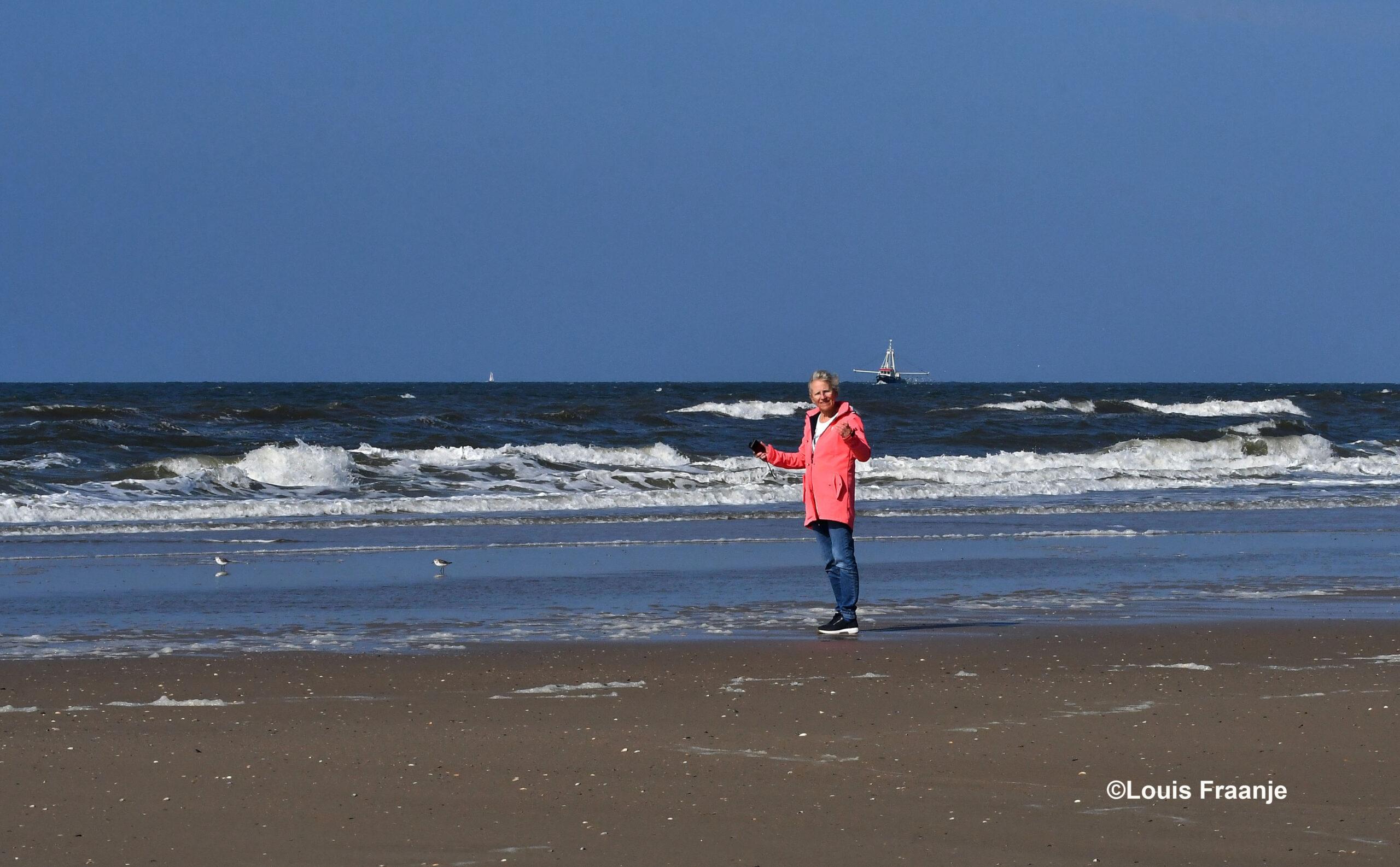 Fransien staat bij de vloedlijn kleine Drieteen strandlopertjes te fotograferen, met op de achtergrond een vissersboot - Foto: ©Louis Fraanje